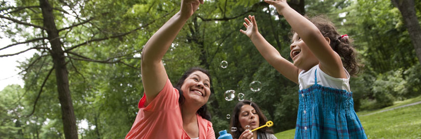 Adults and child playing bubbles