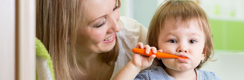 Young child brushing teeth with monther.