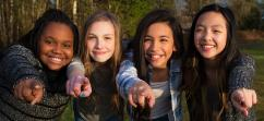 Four teenage girls smiling and pointing towards you.